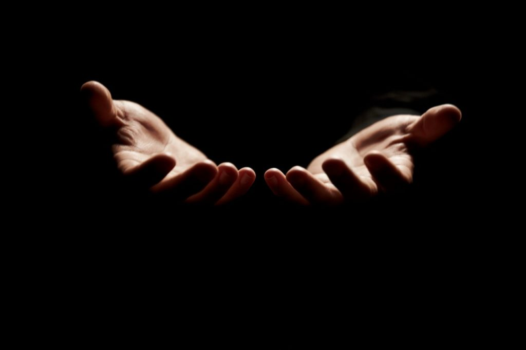 person holding hands out in darkness