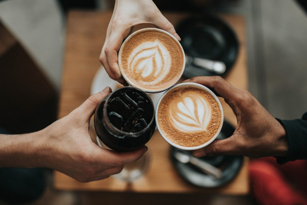 people toasting with coffee and lates