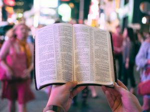 FPV of person holding Bible in front of them in busy city at night