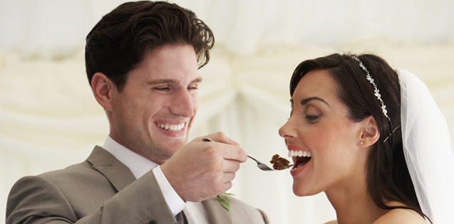 married couple at wedding eating cake