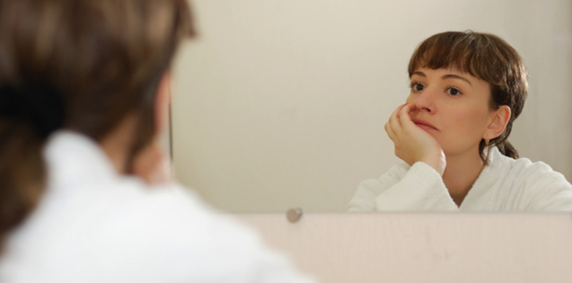woman looking contemplatively in mirror