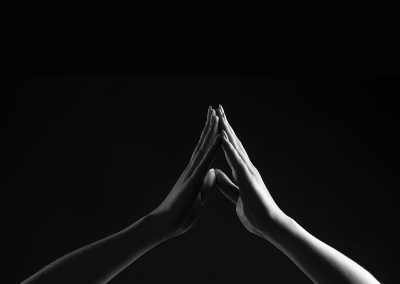 two hands touching in darkness