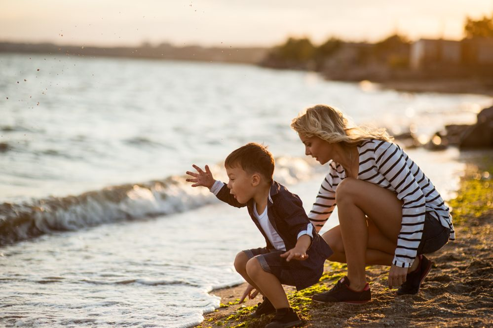 woman and child by beach at sunset