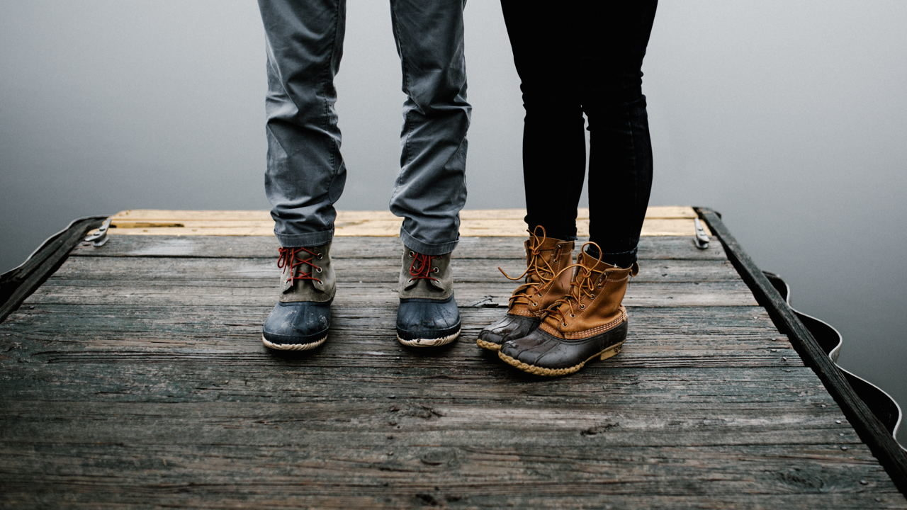 A woman and man standing on a dock, only their boots and lower legs are pictures; rainy day.