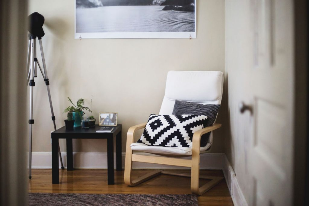 A cozy, modern space with an chair and side table.