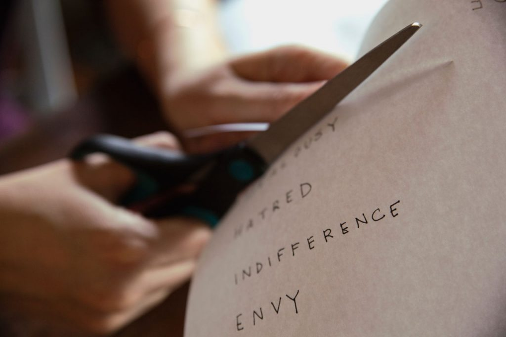 "cutting paper that has words ""hatred"" and ""envy"""