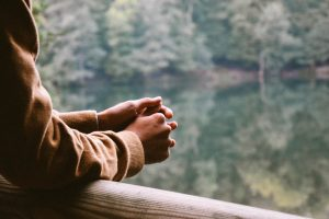 person who's holding hands (praying/thinking), looking off a balcony in the mountains