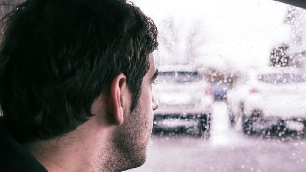 man looking out car window at rain
