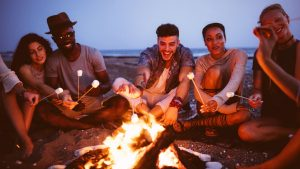 friends sitting around a bonfire, one dating couple sitting close