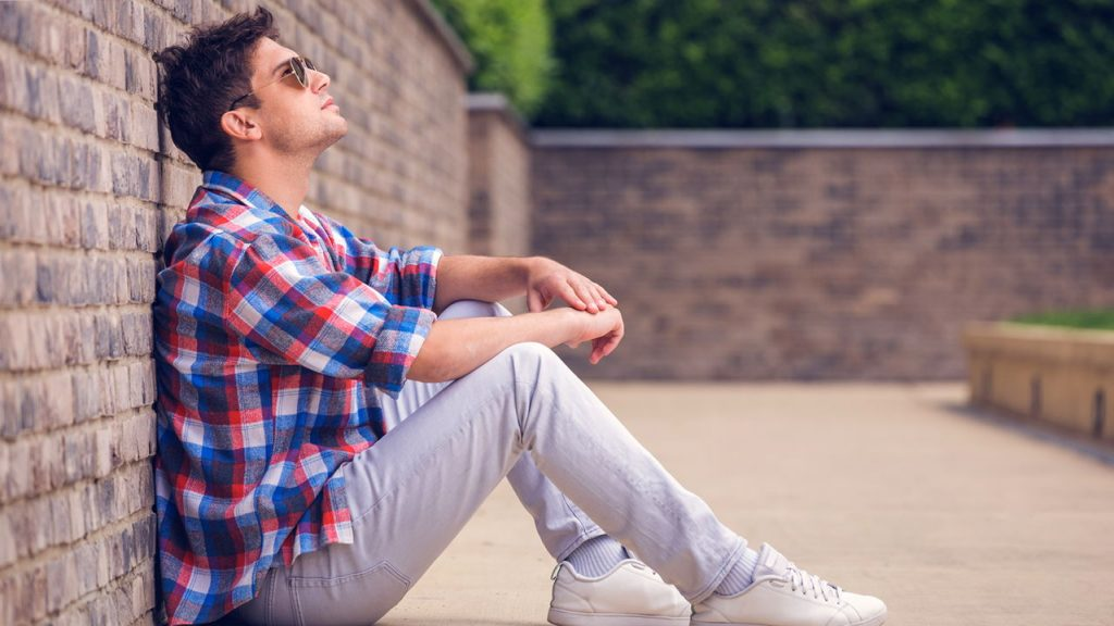 single young guy sitting against a brick wall