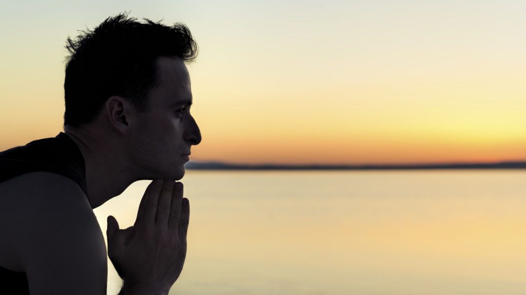 man sitting at beach during sunset looking contemplative
