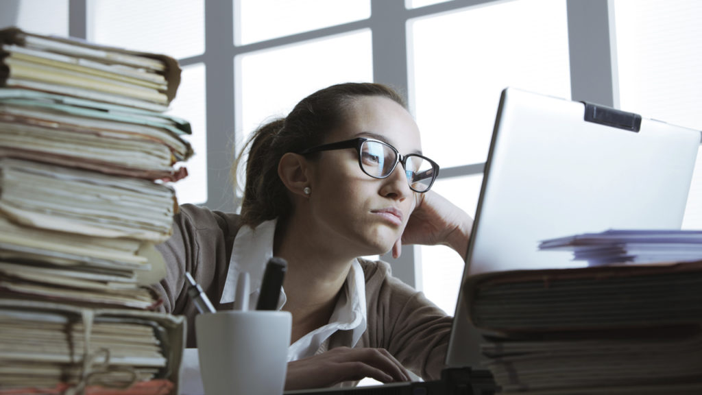 young woman staring at work computer looking bored