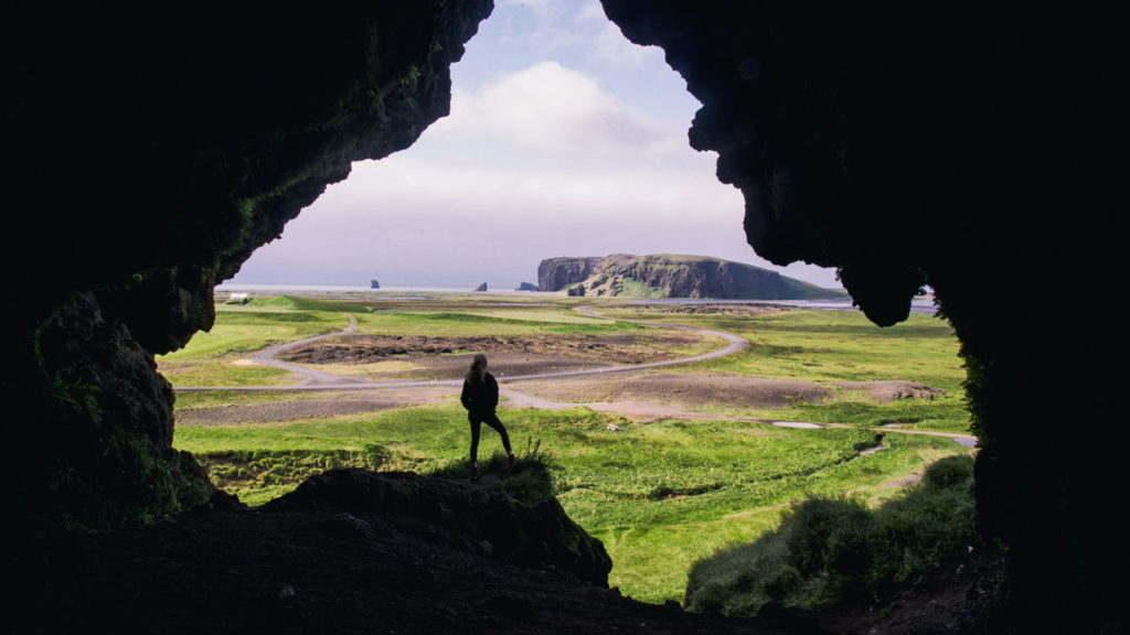 person looking over field from the mouth of a cave