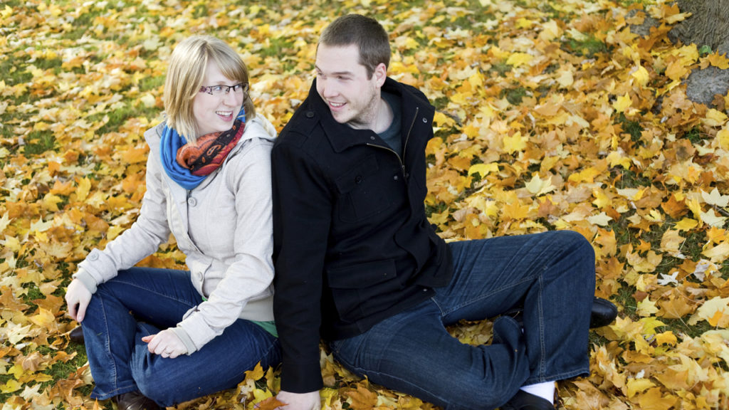 couple sitting on patch of fallen leaves