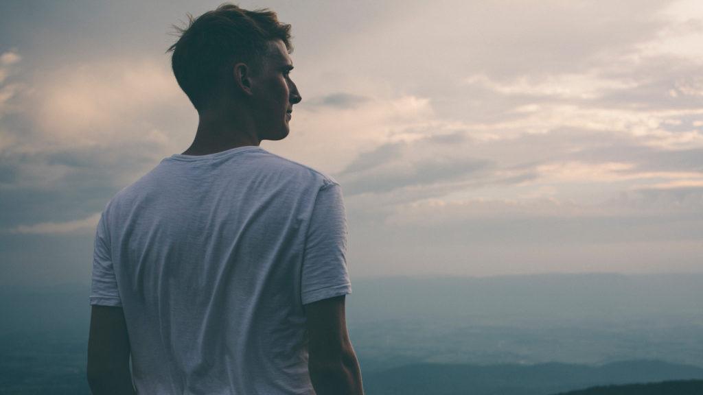 young man looking over ocean